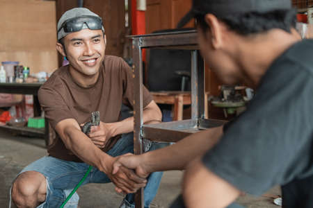 welder and the customer shake hands after completing the iron rack order