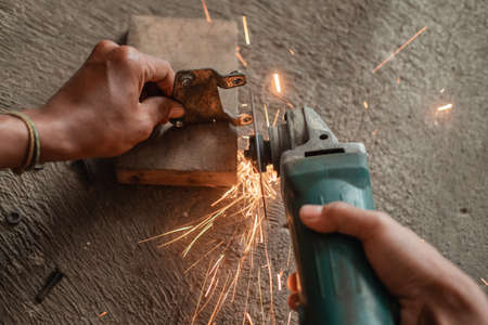 close up of welders hand using a grinder to smooth the surface of the iron hinge