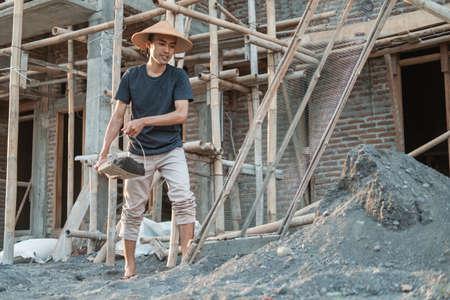 mason holding shovel while carrying sand