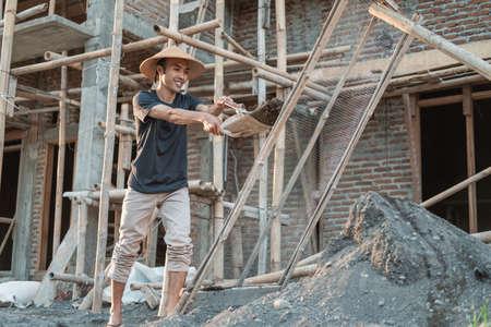 mason holding shovel while carrying sand to sieve