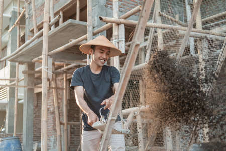 builder holds shovel while bringing sand to sift on strimin wire