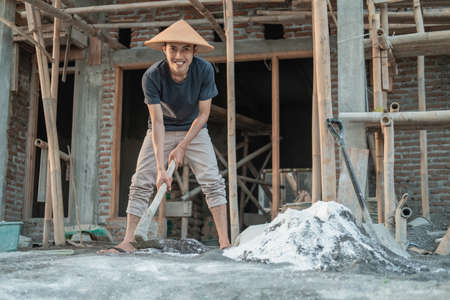 Asian mason holding a hoe for dough for sand and cement for buildings Standard-Bild