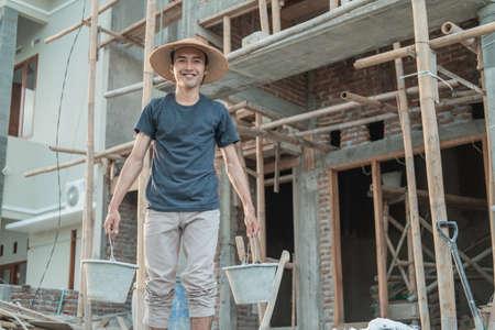 masons wear smiling hats while carrying buckets Standard-Bild
