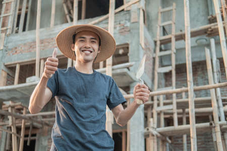 The mason wears a smiling cap with a thumbs up and holds a cement taper