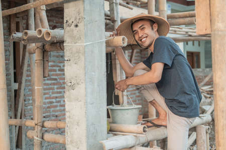 The mason smiles at the camera as he carries buckets filled with cement and sand dough Standard-Bild