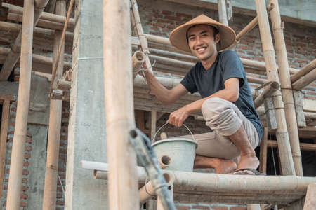 construction workers smile at the camera as they squat on the bamboo planks for wall stucco Standard-Bild