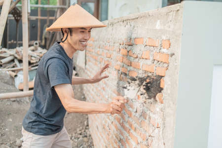 Construction workers use scoops to attach cement to the bricks