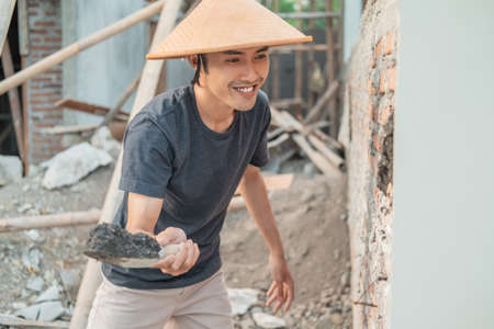 Asian construction workers use a cap using a scoop to attach cement to the bricks