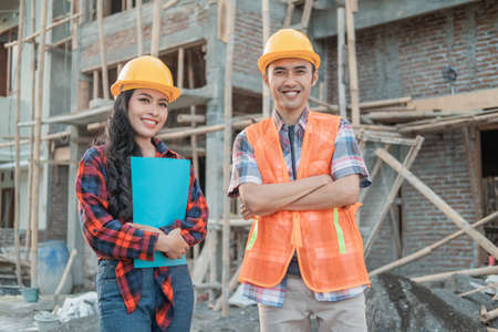 Asian construction workers smiling men and women at the camera wearing vests and safety helmets
