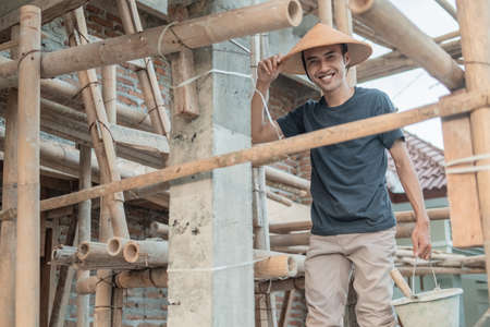 construction workers smile at the camera as they stand between the bamboo and poles Standard-Bild