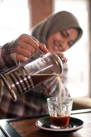 asian female pour coffee into glass. Stok Fotoğraf