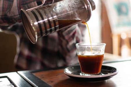 closeup asian female pour coffee into glass.