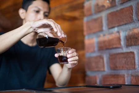 closeup man pour coffee into glass. Stok Fotoğraf