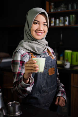 close up of female waitress holding coffee.