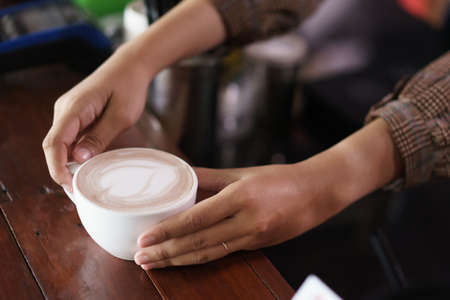 hand holding coffee cup.