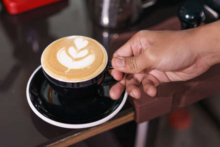 Hand holding cup of coffee.