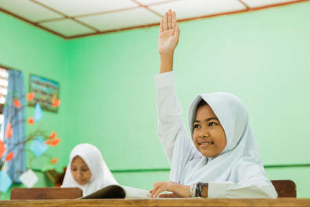 Indonesian primary school student raising hands in the class
