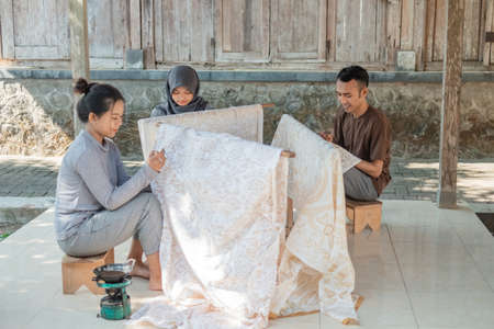 young womans and man together drawing batik