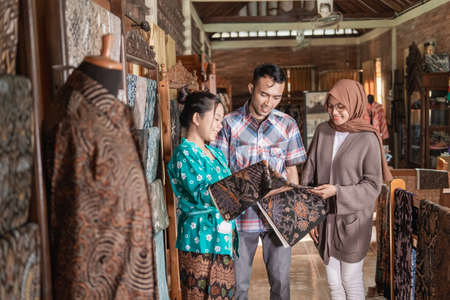 woman showing the traditional batik cloth she sells to customer