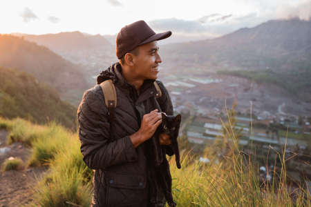 Portrait adventurous man with a backpack captures the moment with cat.