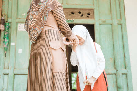 muslim student shake and kiss her mother hand before going to the school