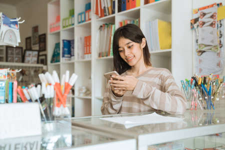 Portrait cheerful young girl entrepreneur texting phone