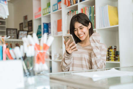 Portrait cheerful young girl entrepreneur happy to see orders via cellphone Stock Photo