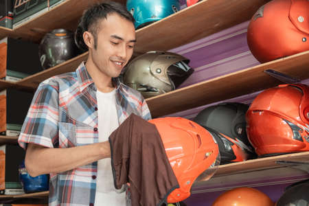 male shop assistant stands cleaning a helmet with a cloth