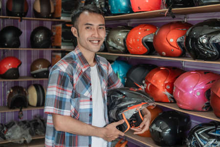 Man smiling standing while holding helmet
