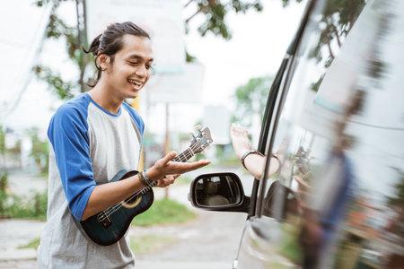 man busker playing on ukulele at city road