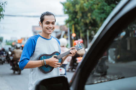 busker use musical instruments and sing in front of the car on the traffic lights crossroad