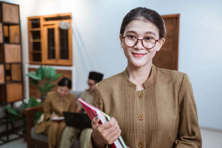 female teacher in civil servant uniform wearing glasses smiling while carrying a book