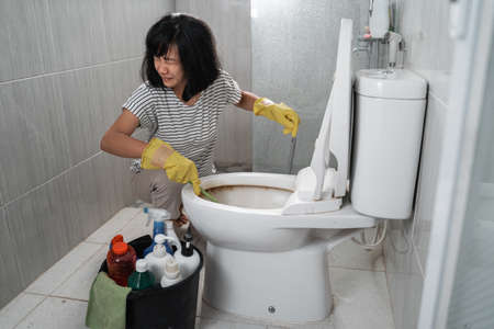 an annoyed woman wearing gloves brushing the dirty toilet