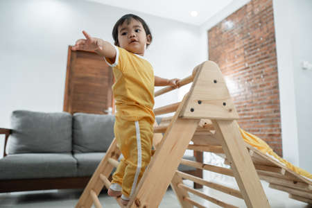 baby is afraid to reach out for help while climbing on the pikler triangle toy