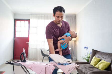 father ironing his clothes while holding his infant baby on his hand