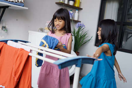 two children having fun doing laundry