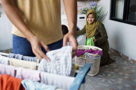 muslim woman and her husband doing laundry together