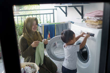 mother a housewife with a baby engaged in laundry