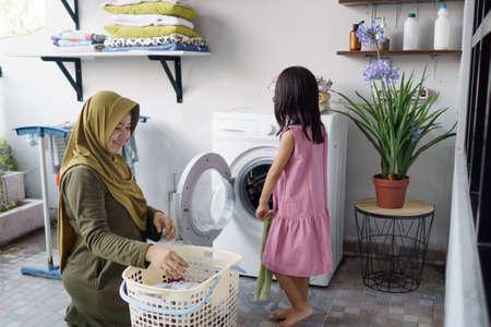 muslim asian mother and child girl little helper in laundry room Reklamní fotografie