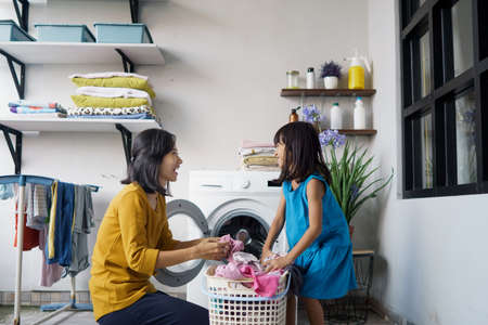 asian woman and child girl little helper are doing laundry at home.