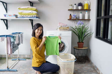 smiling happy asian woman in front of the washing machine Reklamní fotografie