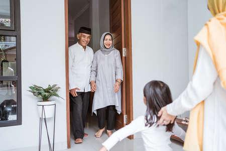 asian muslim aged couple meeting kids and grand children at doorstep during eid mubarak