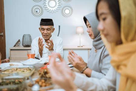 亚洲穆斯林家庭在斋月期间吃开斋餐前祈祷