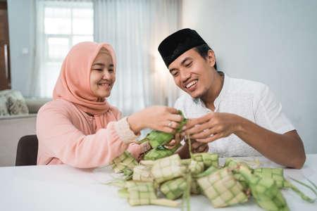 beautiful muslim couple asian making ketupat rice cake at home Stock Photo