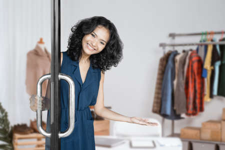 attractive young asian woman welcoming customer to her small shop