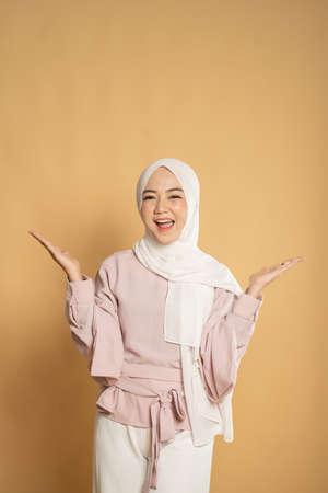 muslim woman euphoric raising arm on studio shot