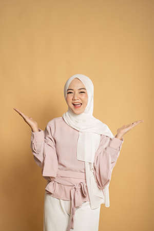 muslim woman euphoric raising arm on studio shot
