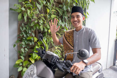 muslim male going to the mosque by riding motorbike Stock Photo