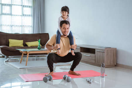 man doing squat while carrying his daughter