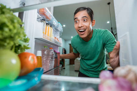 excited starving young asian man opening the fridge door looking for food to eat Standard-Bild